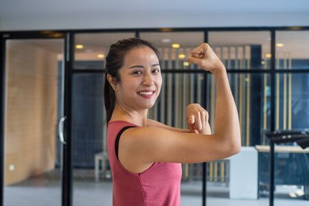 The girl in the gym stretches the muscles, shows strength, good health and smiles in the gym. Exercise healthy concepts