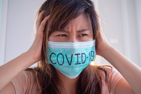 masked woman write Covid-19 has a fear of being infected virus and psychotic symptoms. The situation of the 2019-nCoV virus infection spreading around the world. mask to protect