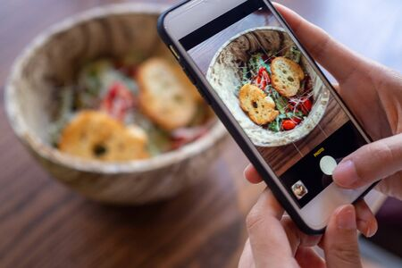 Woman using mobile phone to take pictures of food on the table. Taken on mobile and put on social networks.Take picture concept Foto de archivo