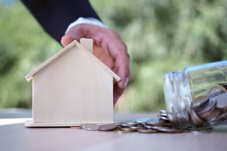 Businessmen caught the house model and the money flowed out of the bottle. Saving money concept