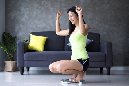 Beautiful Asian women are happy after measuring body weight on scales. The result of success from weight loss to create slim shape and good health. diet concept
