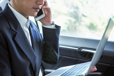 Business people talk on the phone and search for information on a laptop while traveling to negotiate off-site business. Foto de archivo