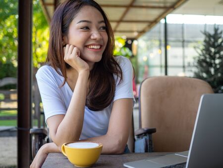 Beautiful and cute Asian women smile brightly and happily while working at the computer in a cafe. Foto de archivo