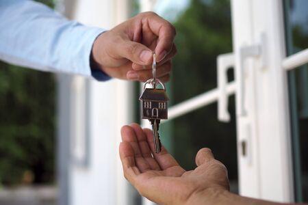 Hauskäufer nehmen die Schlüssel von den Verkäufern mit nach Hause. Verkaufen Sie Ihr Haus, mieten Sie ein Haus und kaufen Sie Ideen. Standard-Bild