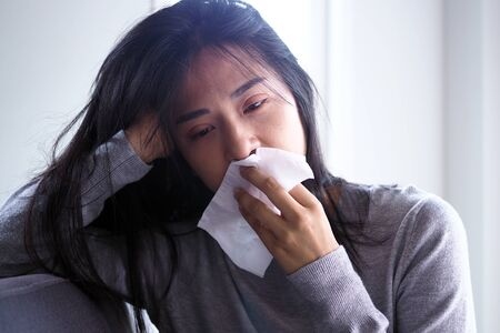 Asian women have high fever and runny nose. Concept of sick people at home