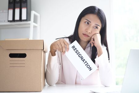 A young businesswoman is bored and thinks of sending a resignation letter.