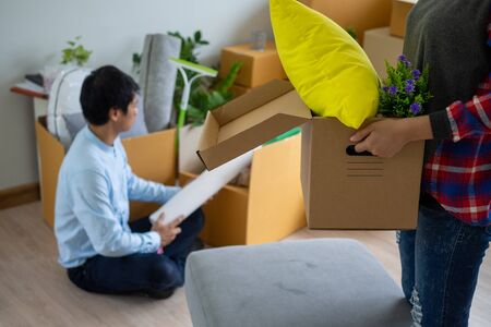 The wife is carrying the box for personal items and the husband is packing the box. Couples prepare to move to a new home. Stock Photo