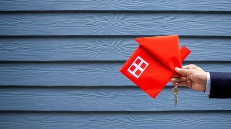 The concept of a business person buying a house or seller house and a red house in hand.