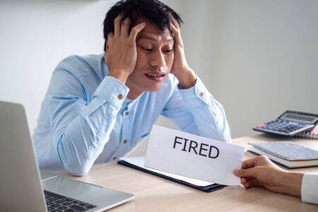 A business man looks and shows signs of stress and panic when the boss sends a dismissal letter. The concept of being laid off