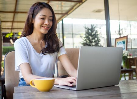 Asian woman pretty face wearing a white shirt, sitting and working in a coffee shop.