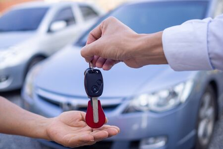 The car salesman and the key to the new owner. Stockfoto