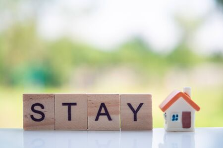 """""""STAY"""" quotes on modern wooden blocks on a natural scenery background. And the placement of the small doll to be cute"""