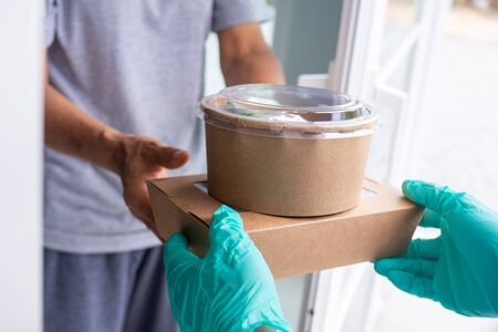 Deliveryman wears the gloves and the mask. Send cardboard boxes containing food to online shoppers. Fast delivery of products or food during detention home. Reduce covid-19 virus outbreaks