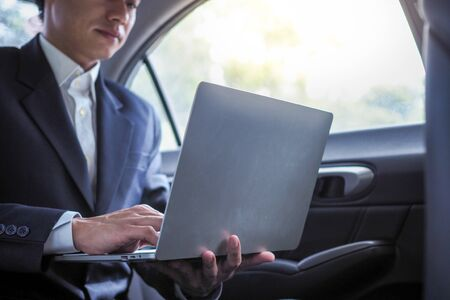 Executives use laptops to work while traveling and sitting inside the car.