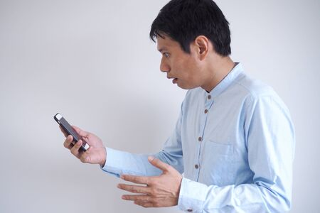 The image of an Asian man looking startled at seeing a message on his mobile phone or reading startling news