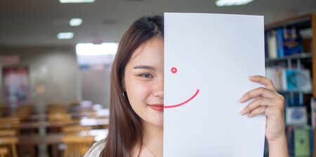A beautiful female student in Asia holds a paper drawing a smile with red ink and a happy posture on campus. Foto de archivo