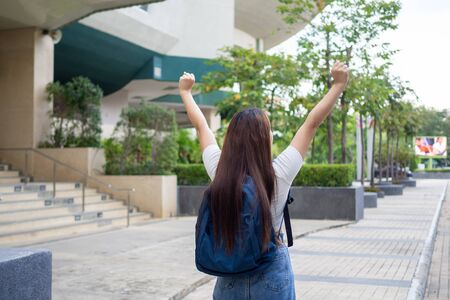 Asian female student relaxed posture felt very happy after school during the break. Carrying a backpack, ready to go home.