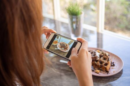 The female hand took a photo of the chocolate-covered waffles in the coffee shop and prepared to upload to a social app Foto de archivo