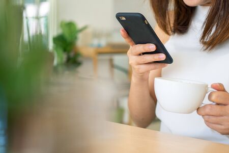 A woman is sitting and drinking coffee in the house and using a mobile phone to scan for an online store. Shopping. Buying ideas online is fast and convenient. No need to go to the store. Foto de archivo