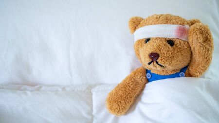 The teddy bear was sick in bed after being injured in an accident. Getting life insurance and accident insurance concept