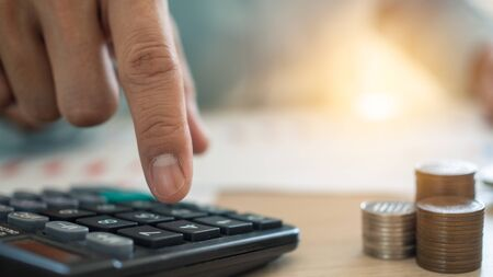 The man's finger that presses the calculator to calculate and analyze income and expenses the growth of coins and financial costs, wisely and prudently, the concept of investment ,savings and debt Foto de archivo