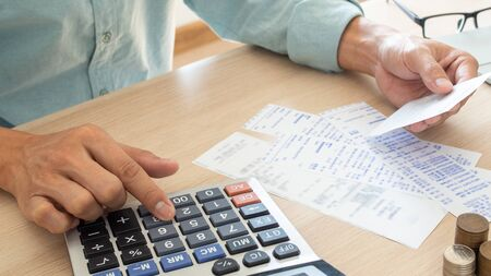The butler is pressing the calculator calculate the various costs that must be paid by the bill. Many invoices held and placed on the table Foto de archivo
