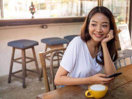 Asian long haired woman wearing a white shirt sitting in a coffee shop cheerful and bright smile. Foto de archivo