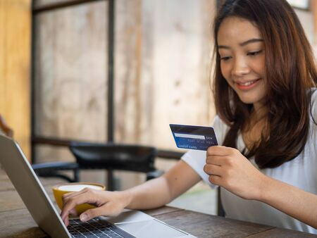 Woman using credit card to shop online. shoping personal belongings through various web application applications in notebook. Foto de archivo