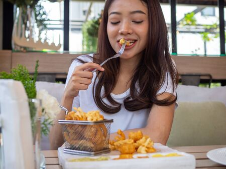 A beautiful Asian woman is eating fries with a happy feeling and enjoying eating in a modern loft.
