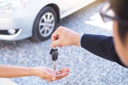 Les hommes d'affaires envoient des clés de voiture aux nouveaux propriétaires.