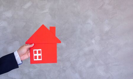 The concept of a business person buying a house or seller house and a red house in hand. Advice on how to plan a house for new hire buyers
