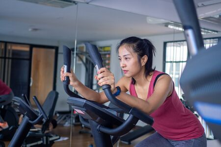 Woman electric bicycles in at fitness gym, Young woman workout in gym healthy lifestyle