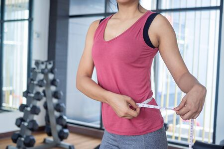 Diet women are measuring waist with tape in the gym. Exercise concept for good health and beautiful shape