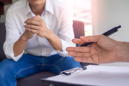 The image focuses on the psychiatrist's hand. The clipboard records the illness. Is healing the minds of male patients counseling for mental illness