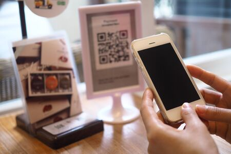Hand using the phone to scan the QR code to receive discounts on government tourism programs. Foto de archivo