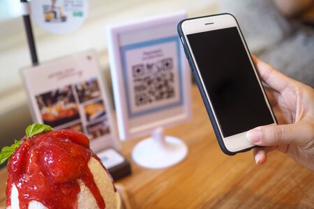 Hand use the phone to scan the barcode to get the discount in the cafe shop