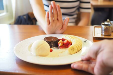 Man hands sending Bingsu to a woman. But women push their hands. She denied eating all kinds of sweets. Avoid sugar and desserts for good health concept.