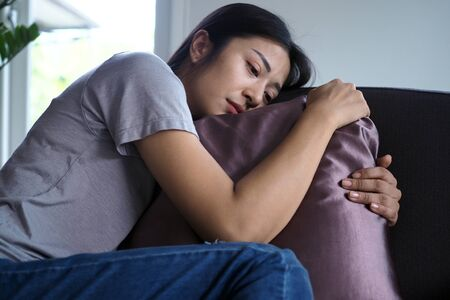 Asian women sitting on the couch. Women are confused, disappointed, sad and sad.