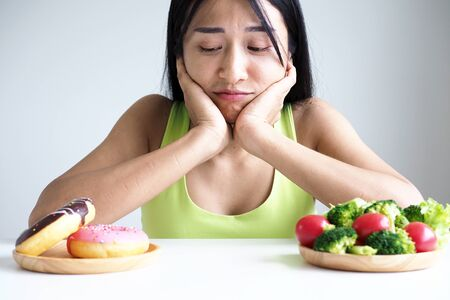 Asian beautiful women choose between vegetables and donuts. lose weight