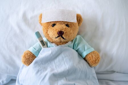 Sick bear is wearing patient clothes. lying in bed with fever, a fever-reducing gel on his forehead and at the temperature temple, put it under the armpit