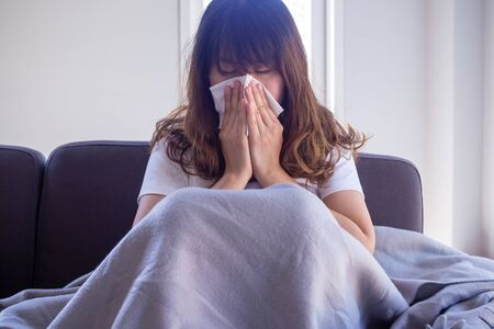 Long haired woman sitting on the sofa is suffering from flu, cough and sneezing. Sitting in a blanket because of high fever and cover their nose with tissue paper because sneezes all the time.