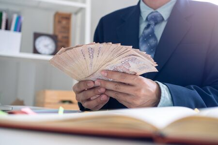 Businessmen sit counting money in baht in the office, preparing to distribute salaries and bonuses or contributions to employees in the company. Employee Assistance Fund for Thai people