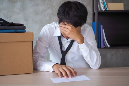 Businessmen sit stressed and very upset with the termination letter. The problem of getting fired