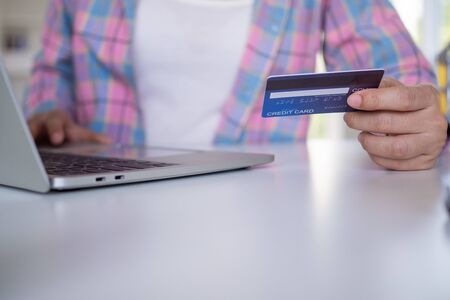 Woman holding a credit card to pay for goods through an application on a laptop. Online shopping and payment on internet banking by credit card. online shopping at home concept Foto de archivo