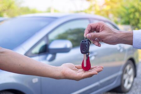 The owner sent the car keys to the renter's hands. There is a car parked in the back. Rent or buy concept