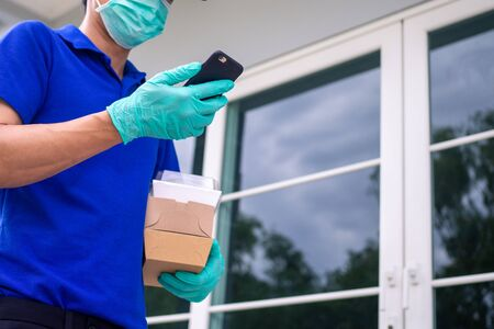 The delivery man holding a paper box, wears a mask and wears rubber gloves stand front home of customer and check order online in smartphone. Transportation Fast and free delivery online shopping.