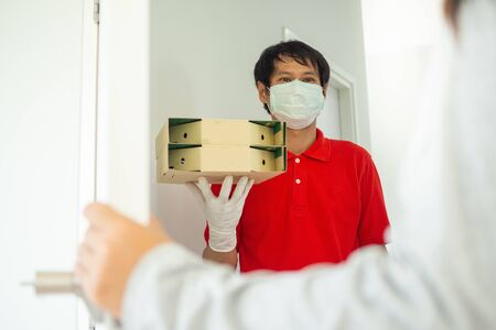 The delivery man wears a mask and gloves, delivery food to the home of the online buyer. eat at home in breakfast. The sender has a service to deliver products or food quickly