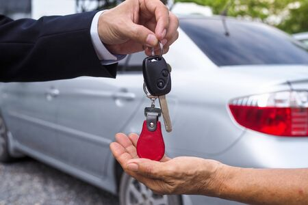 The car salesman and the key to the new owner. Foto de archivo