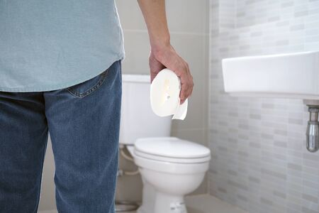 Man holding toilet tissue in the bathroom
