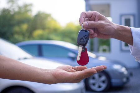 The male salesperson send the keys and car to the customer at home. Concept of selling car and renting cars with good service